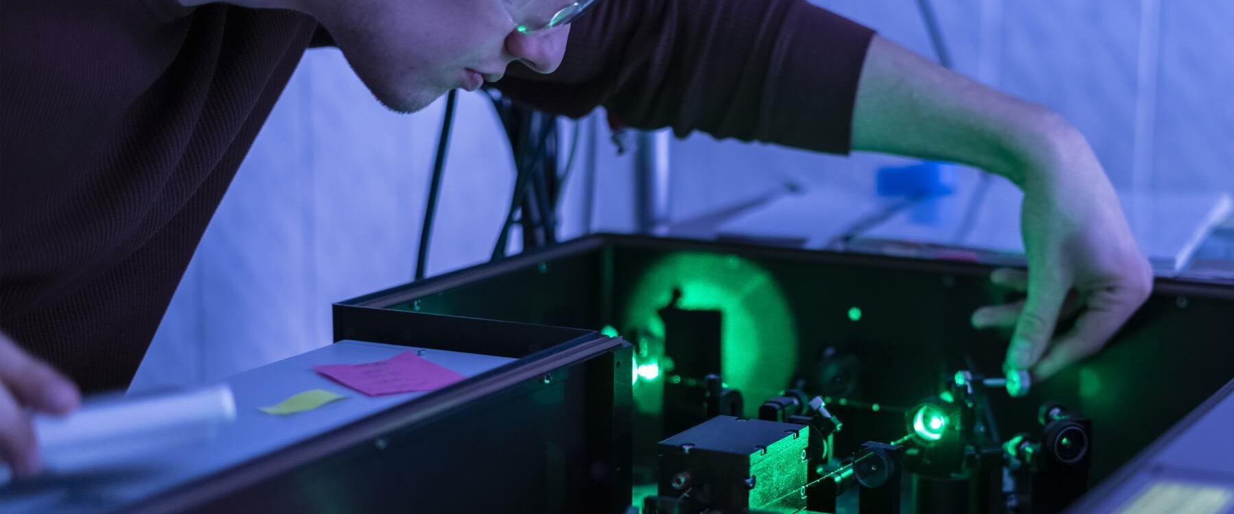 male student working with laser machine