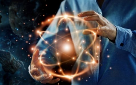 person holding quantum artwork of atomic symbol with fiery glow